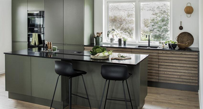 aubo oak line køkken i egetræ sammen med grønne skabe og sort bordplade