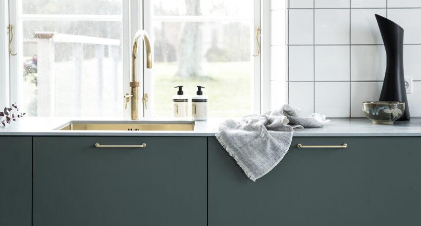 aubo fenix køkken i grøn med grå bordplade og quooker i messing